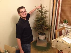 Jon holding the Christmas tree as the pine needles fall off it