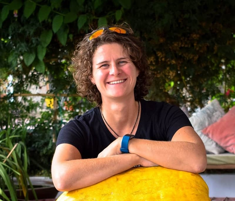 Laura smiling with her arms resting on a giant squash